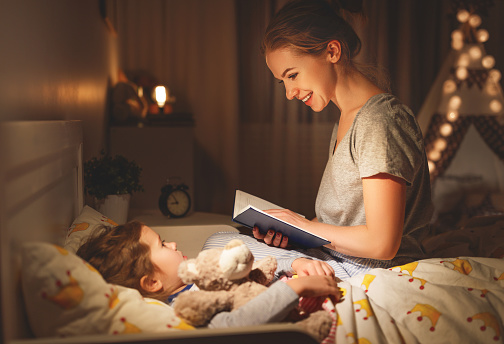 mother and child reading book in bed before going to sleep