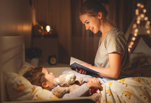 mother and child reading book in bed before going to sleep stock photo