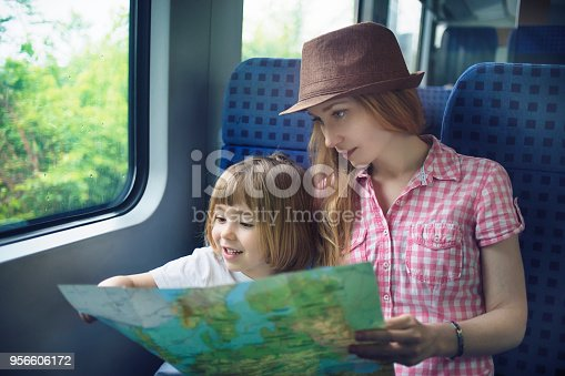 Mother and child reading map while travelling by train in rainy day.