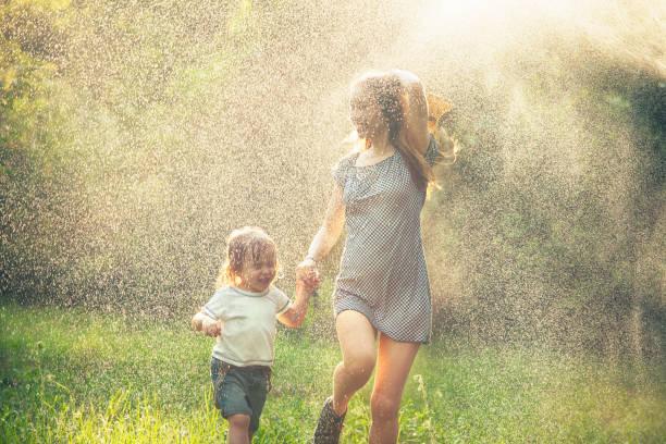 mother and child running in the rain - mãe criança brincar relva efeito de refração de luz imagens e fotografias de stock