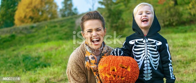 Trick or Treat. smiling modern mother and child on Halloween at the park showing pumpkin Jack O