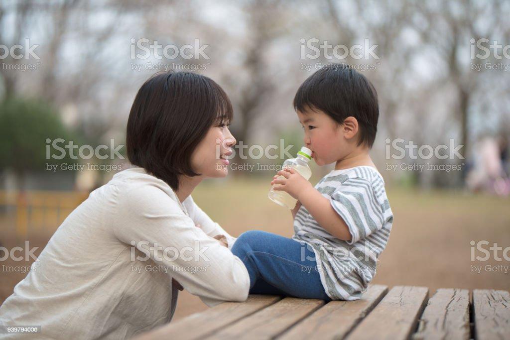 母と子のベンチに座っていると話して ロイヤリティフリーストックフォト