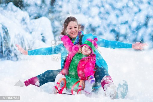 Christmas Vacation Sled.Mother And Child Sledding In Snowy Park During Christmas