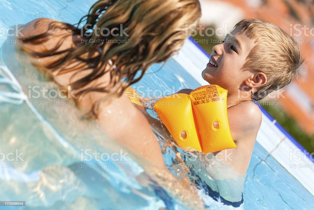 Mother and child swimming in infinity pool royalty-free stock photo