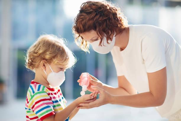 フェイスマスクと手指消毒剤を持つ母と子供 - マスク ストックフォトと画像