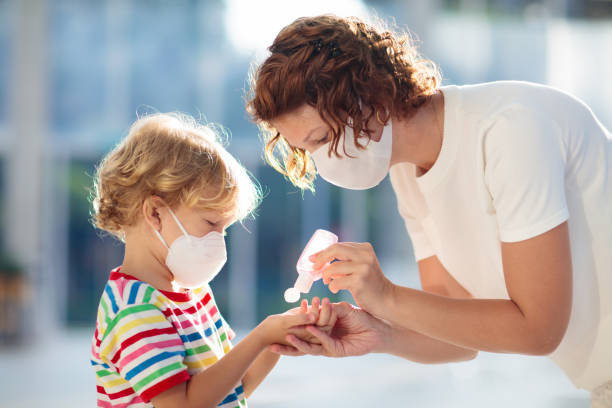 Mother and child with face mask and hand sanitizer stock photo
