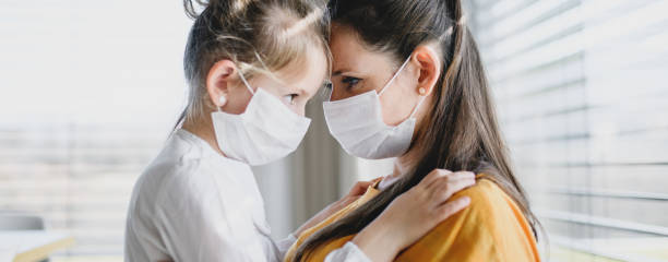 Mother and child with face masks indoors at home, Corona virus and quarantine concept. stock photo