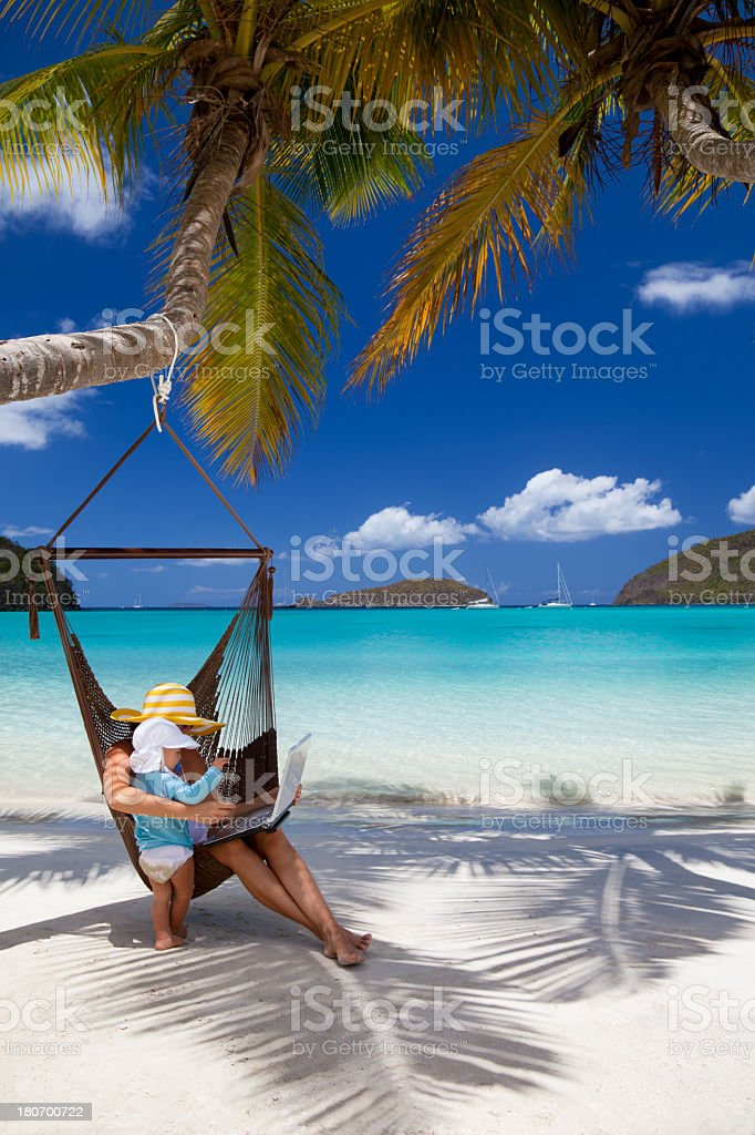 mother and child with laptop relaxing in a beach hammock royalty-free stock photo