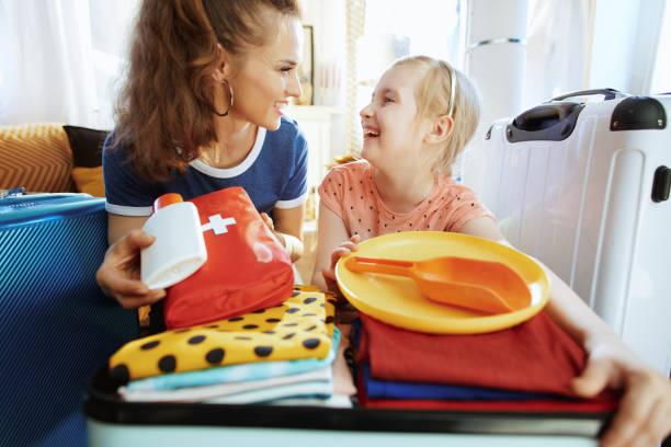 açık bavul bavul ile anne ve çocuk tatil için hazır - kazalar ve felaketler stok fotoğraflar ve resimler