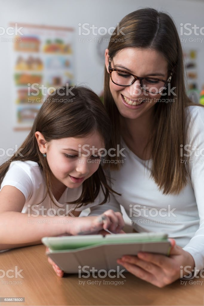 Mother and child with tablet indoors stock photo