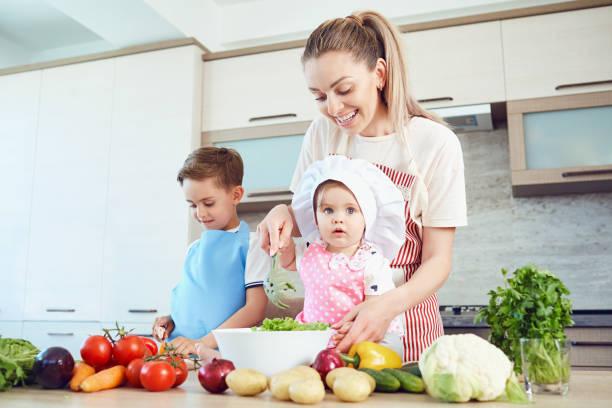 Mutter und Kinder sind in der Küche kochen. – Foto
