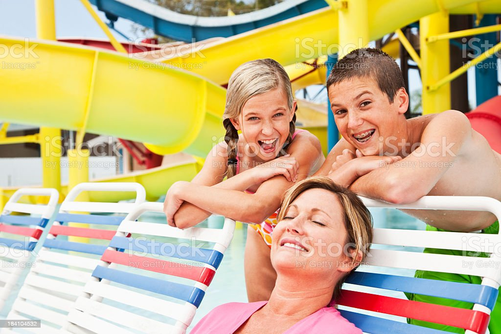 Mother and children at water park Family on vacation, having fun at water park.  Water slide in background 10-11 Years Stock Photo