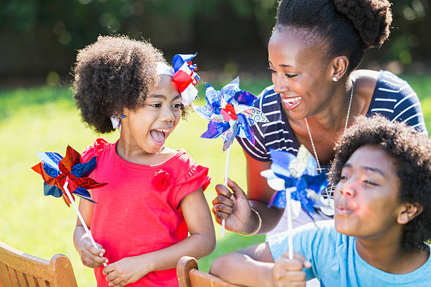 Mother and children celebrating 4th of July An African American mother with two mixed race children celebrating an American patriotic holiday, perhaps July 4th or Memorial Day. They are playing with red, white and blue pinwheels, smiling and laughing, outdoors on a bright, sunny day. The children are black, Asian and Hispanic. family 4th of july photos stock pictures, royalty-free photos & images