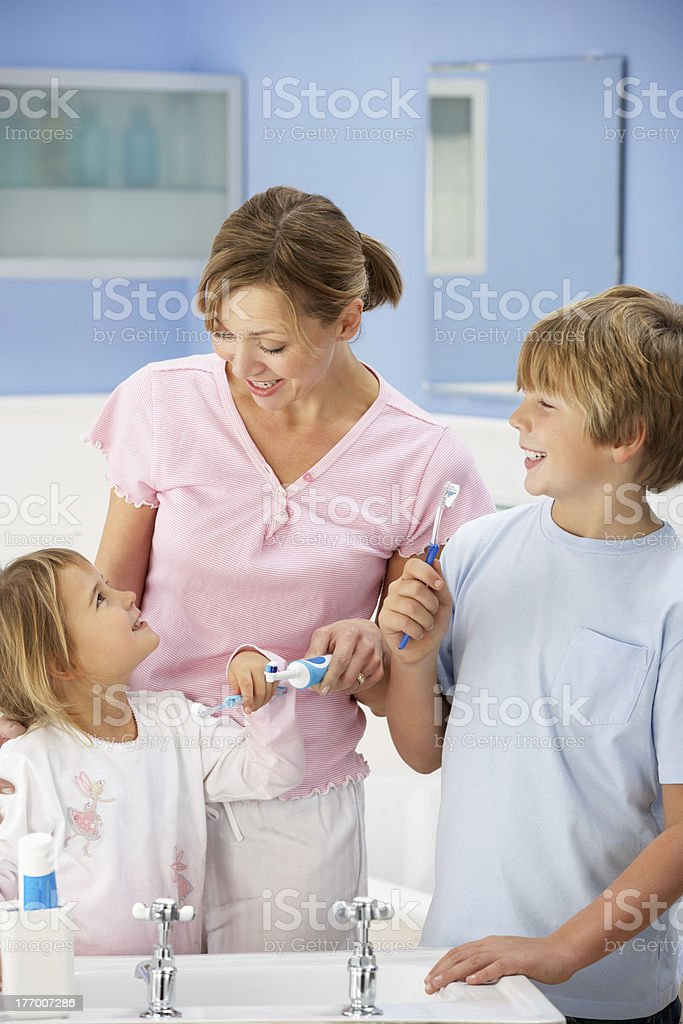 Mother and children cleaning teeth in bathroom royalty-free stock photo