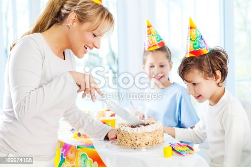Beautiful young mother is cutting the birthday cake while the children are watching with excitement.
