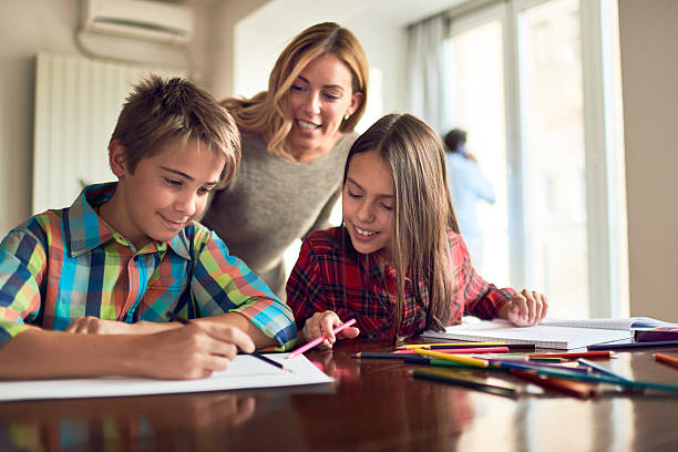 Mother and children doing homework stock photo