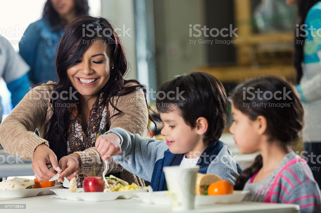 Young adult Hispanic mother is enjoying a healthy meal with her two...