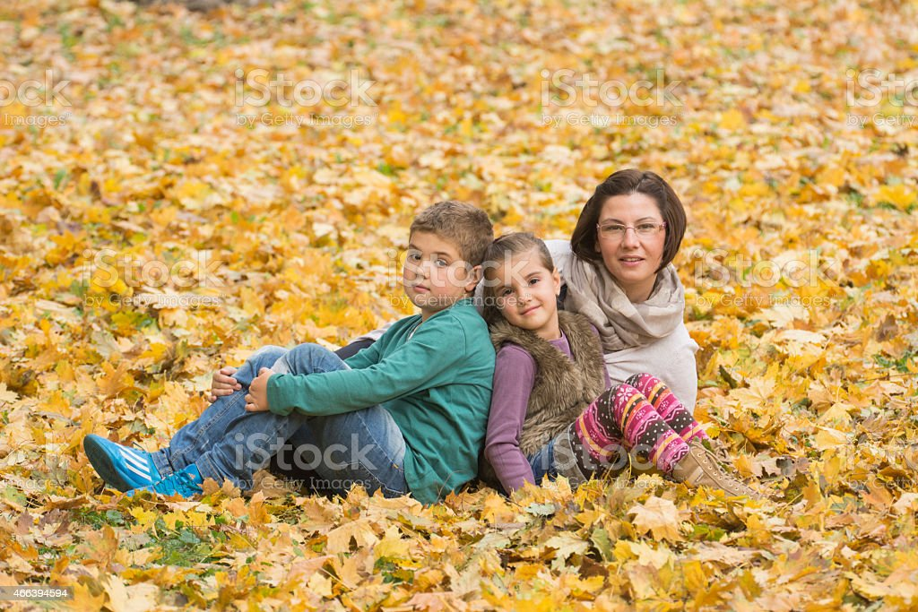 Mother and children enjoying autumn in park stock photo