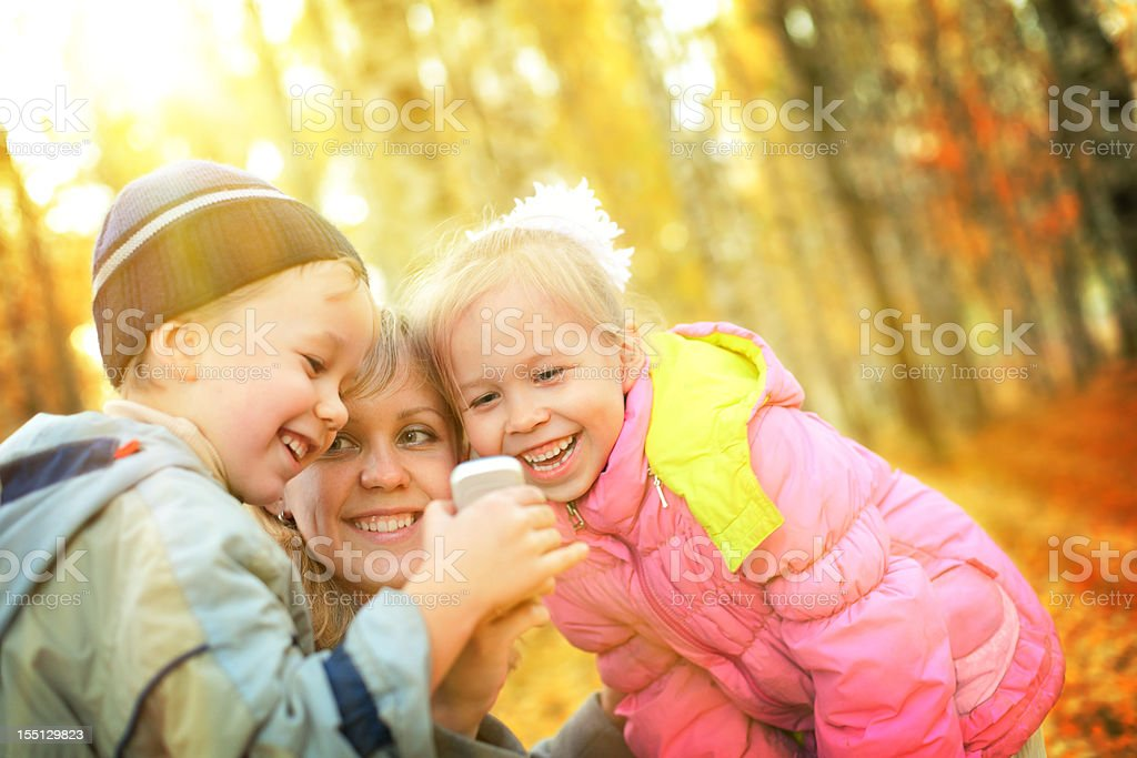 Mother and children having fun in autumn park royalty-free stock photo