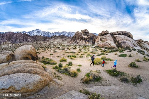 A mother and two children hiking in the Alabama Hills in the eastern Sierra Nevada in California. Lone Pine Peak and Mt. Whitney loom in the distance behind.