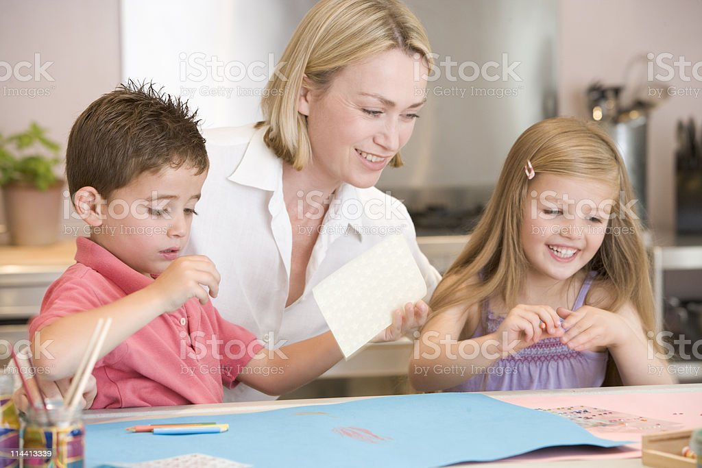 Mother and children in kitchen doing crafts stock photo