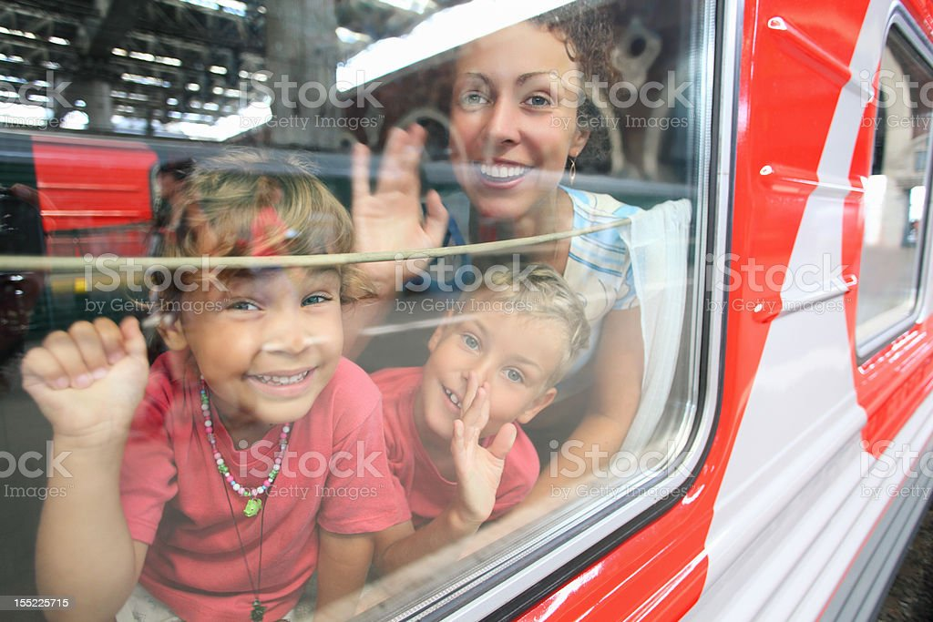 Mother and children look from train window stock photo