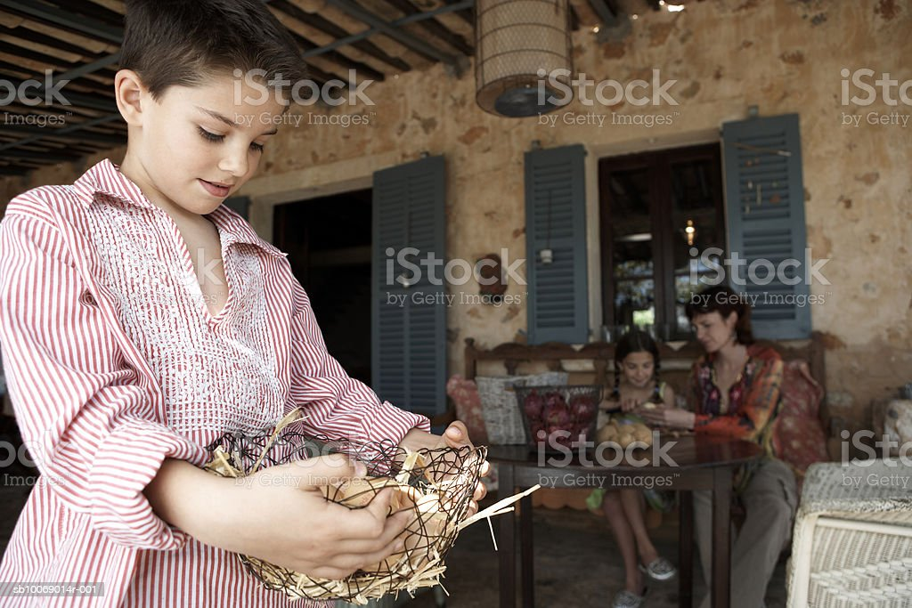 Mother and children (8-9) on porch, boy carrying basket of eggs royalty-free stock photo