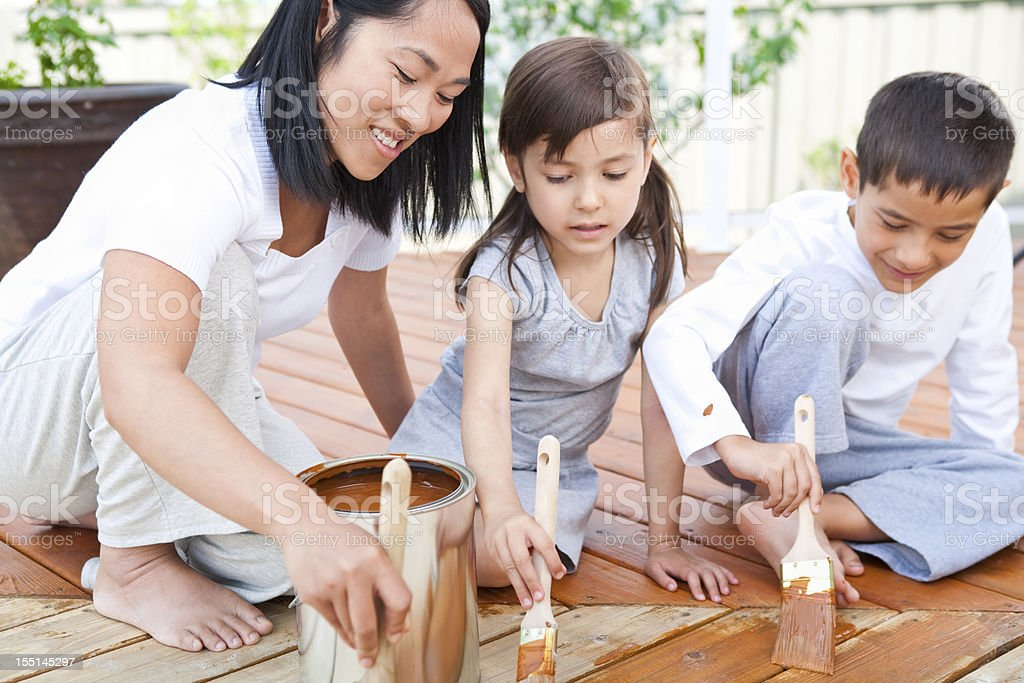Mother and children painting deck stock photo