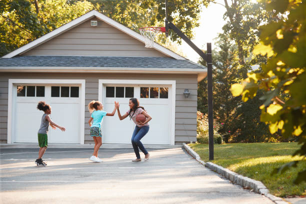 Mother And Children Playing Basketball On Driveway At Home - foto stock