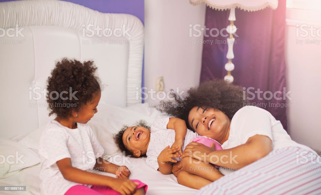 Mother and children playing in bed stock photo