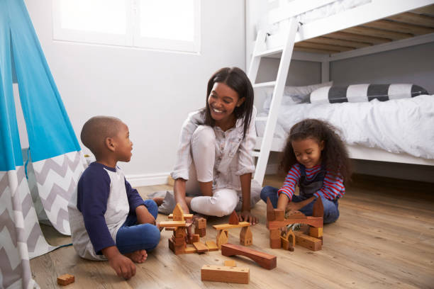 mutter und kinder spielen mit bausteinen im schlafzimmer - tipi bett stock-fotos und bilder