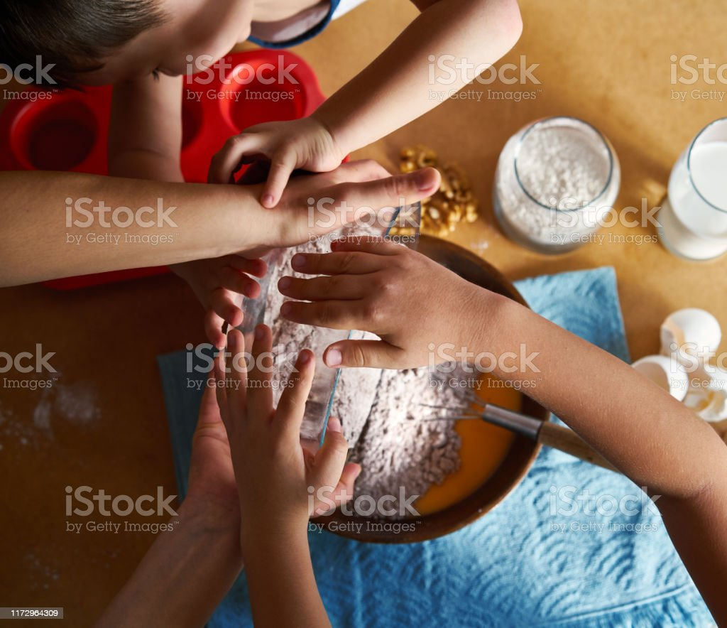 Mother and children preparing cake together Mother and children preparing cake together Baked Pastry Item Stock Photo