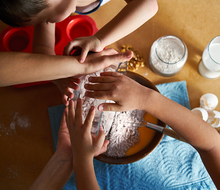 Mother And Children Preparing Cake Together Stock Photo - Download Image Now