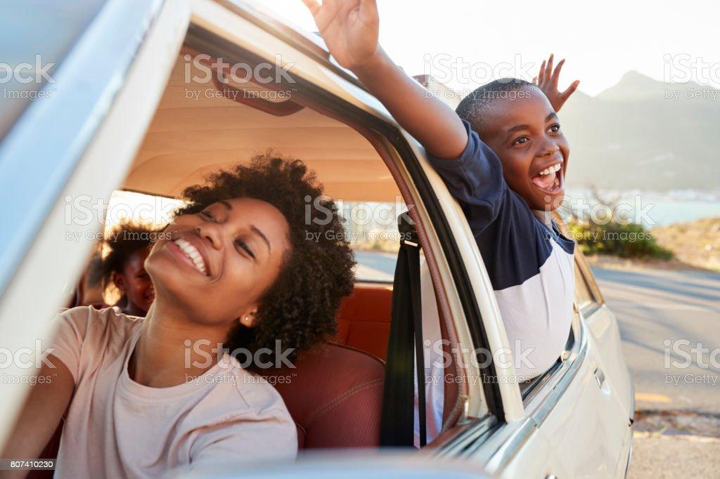 Madre y los niños en coche durante el viaje por carretera - foto de stock