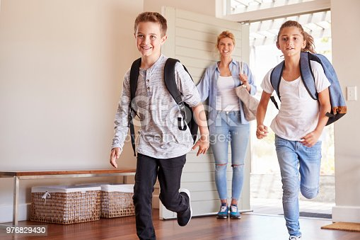 670900812 istock photo Mother And Children Returning Home After School Day 976829430
