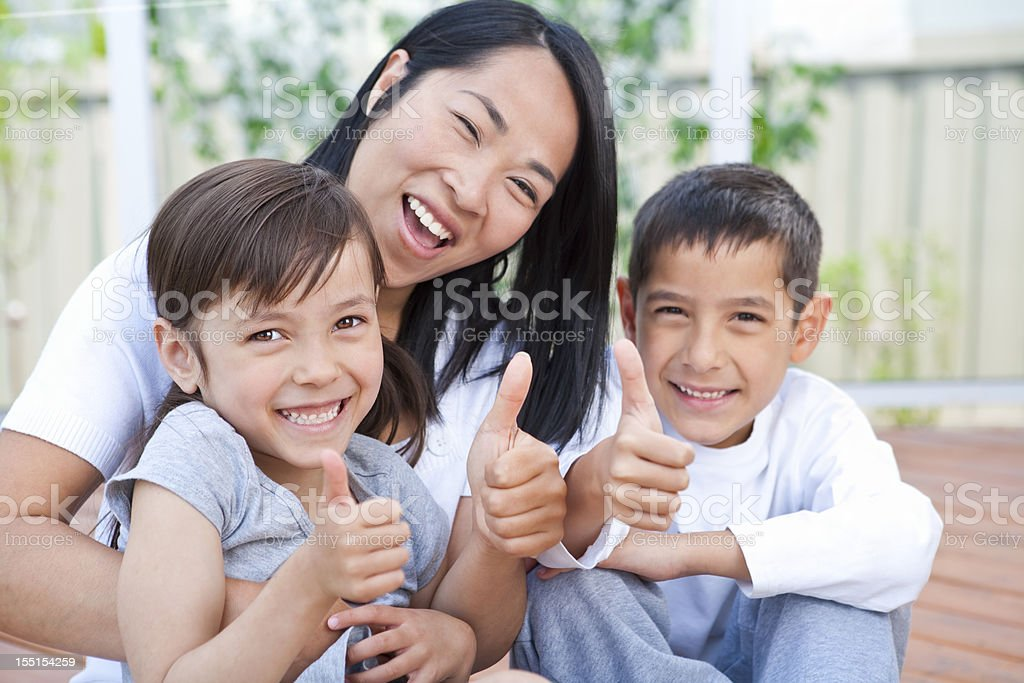 Mother and children sitting on deck putting thumbs up royalty-free stock photo