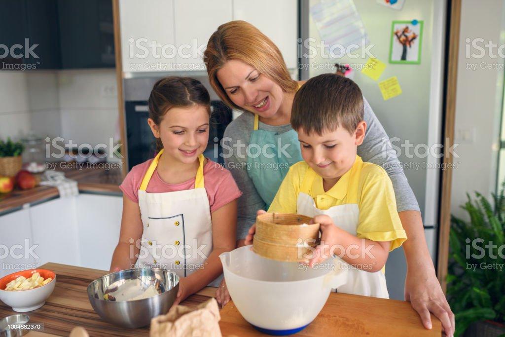 Mutter und Kinder zusammen in der Küche zu Hause Apfelkuchen machen – Foto