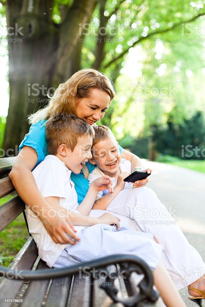 Mother and children using mobile phone in the park royalty-free stock photo