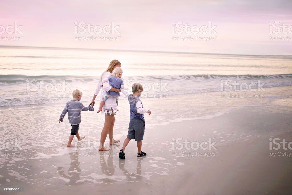 Mother and Children Walking Along Ocean Beach at Sunset stock photo