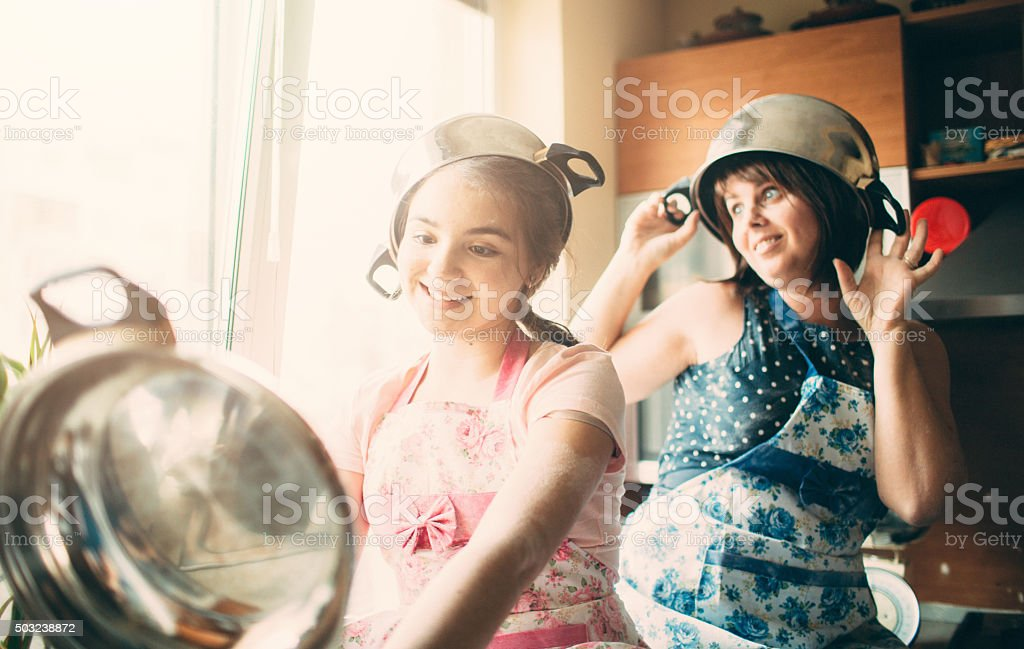 Mother and children wearing saucepans on heads stock photo