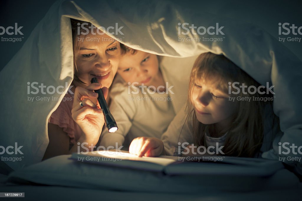 Mother and children with book under bed covers royalty-free stock photo