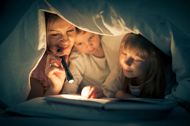 Mother and children with book under bed covers stock photo