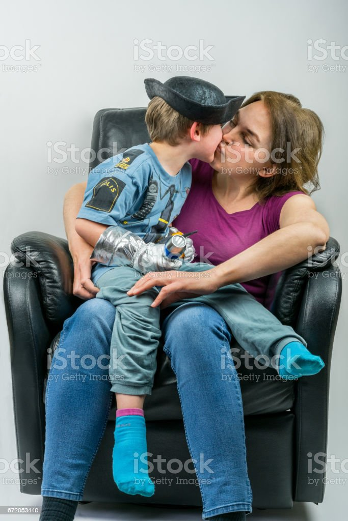 Mother and cute child dressed in pirate and police costume sitting in black armchair. Mother giving her son a kiss. royalty-free stock photo