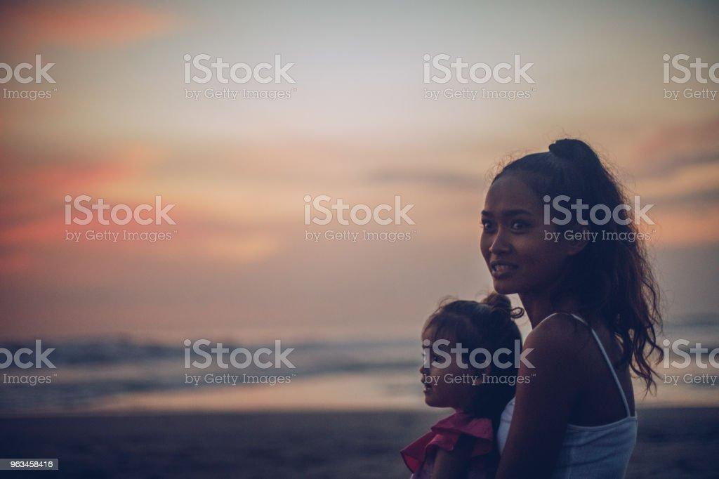 Madre e hija Linda disfrutando del atardecer en la playa - Foto de stock de Adulto libre de derechos
