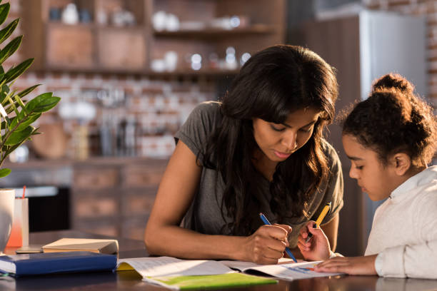 mother and cute little daughter sitting at table and doing homework together at home, homework help concept - homework stock photos and pictures