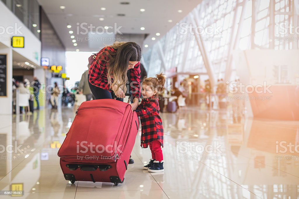 Mother and cute toddler girl pulling together a suitcase stock photo
