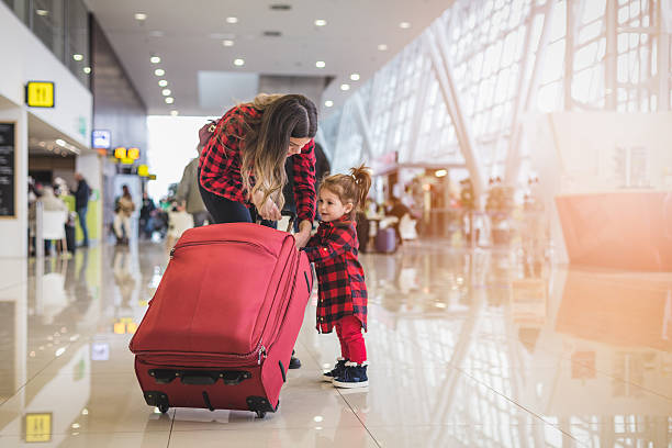 mother and cute toddler girl pulling together a suitcase - babytasche stock-fotos und bilder