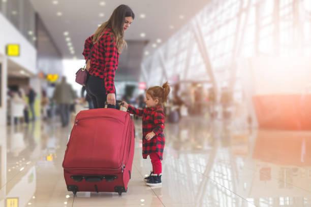 mutter und niedlichen kleinkind mädchen einen koffer an einem strang - babytasche stock-fotos und bilder