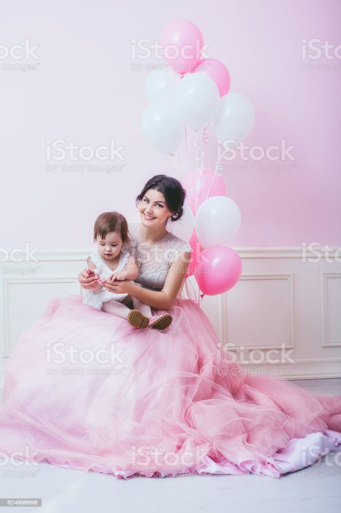Mother and daughter a beautiful and happy pink interior with stock photo