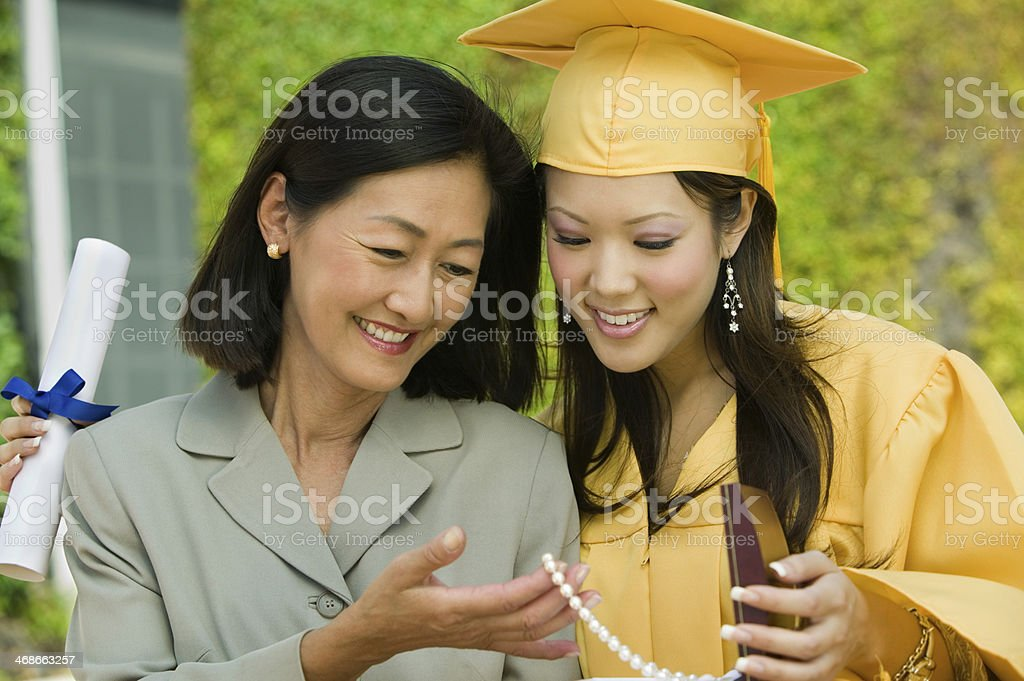 Mother and Daughter Admiring Gift at Graduation stock photo